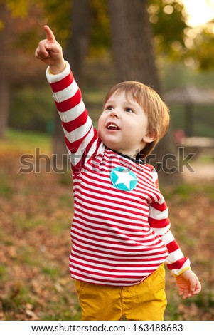 Image of beautiful boy pointing at something, shallow depth of field - stock photo