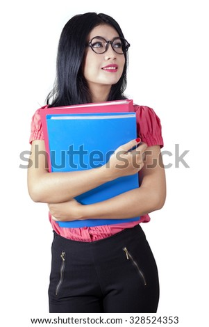 Image of beautiful businesswoman wearing glasses and holding business documents while looking at copy space in the studio - stock photo