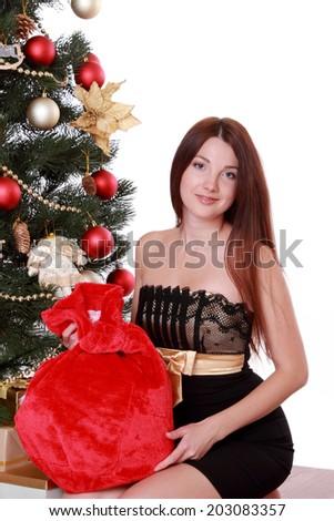 Image of beautiful smiling brunette womansitting over Christmas tree on Holiday theme - stock photo