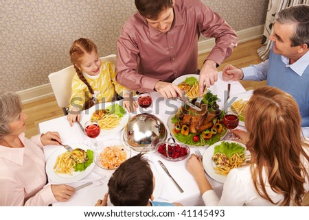 Image of big family sitting at festive table and eating salad and roasted turkey - stock photo