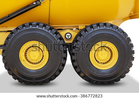 Image of big wheels of mining truck with black tires, isolated on white background - stock photo