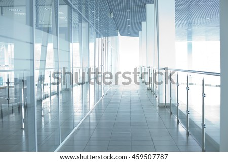 Image of big windows passing daylight inside office building. Sunny on modern glass windows building interior corridor - stock photo