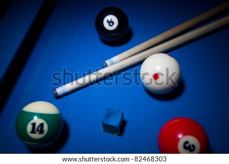 Image of billiard balls, cue and  chalk on blue table - stock photo