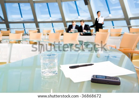 Image of blank papers, pen, cellular phone and glass of water on table of conference room - stock photo