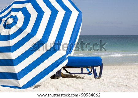Image of blue lounge chair and blue and white striped umbrella set against the South Beach Atlantic shoreline in the late afternoon in Miami Beach. - stock photo