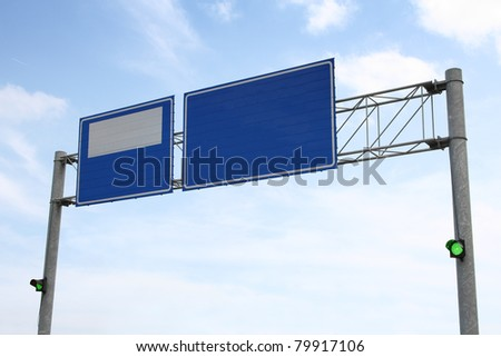 Image of blue road sign with green traffic lights on - stock photo