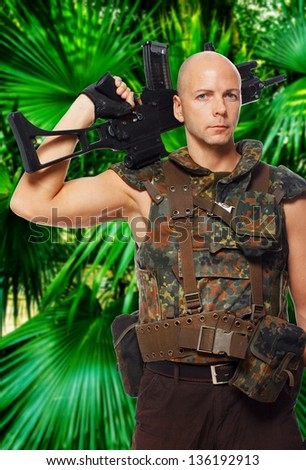 Image of bold soldier with rifle in the jungles - stock photo