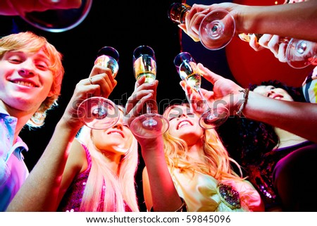 Image of boozing young people with champagne flutes toasting at party - stock photo