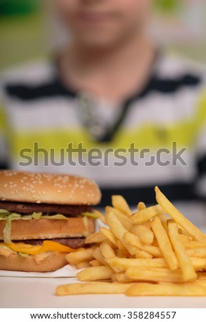 Image of boy and unhealthy caloric junk food - stock photo