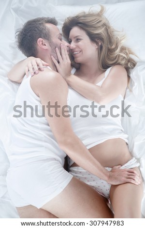 Image of boyfriend and girlfriend having fun lying in bed - stock photo