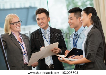 Image of business colleagues discussing something during the break of the meeting - stock photo