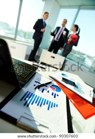 Image of business documents on workplace with three partners on background - stock photo