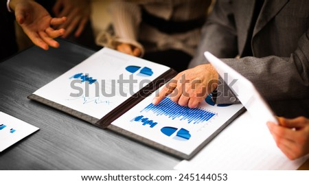 Image of business documents with working team communicating at background - stock photo