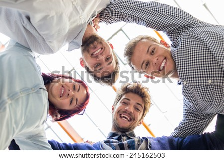 Image of business friends discussing brainstorming and ideas at meeting inside beautiful modern building place in circle holding each other - stock photo