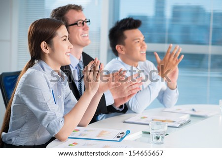 Image of business partners applauding at the meeting sitting in a line - stock photo