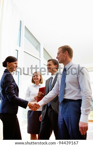 Image of business partners handshaking after signing new contract - stock photo