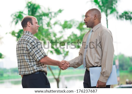 Image of business partners handshaking in sign of successful cooperation  - stock photo