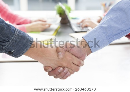 Image of business partners handshaking over business objects on workplace  - stock photo