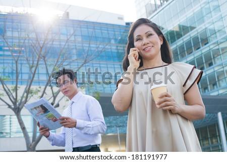 Image of business people having break outside  - stock photo