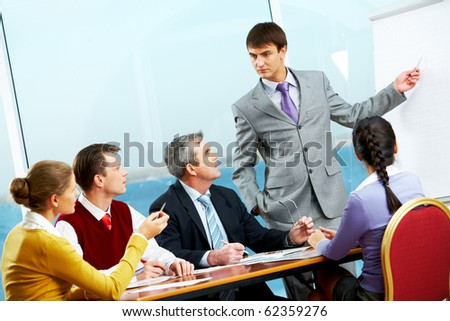Image of business people listening to businessman showing at whiteboard - stock photo
