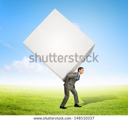 Image of businessman carrying big white cube on his back - stock photo