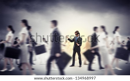 Image of businessman in blindfold walking among group of people - stock photo