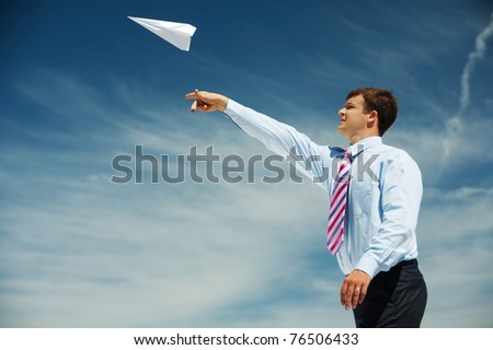 Image of businessman letting paper airplane fly and looking at it on background of blue sky - stock photo