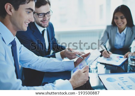 Image of businessman pointing at document in touchpad while interacting with his partner at meeting - stock photo