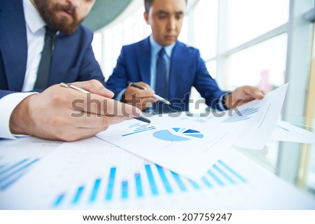 Image of businessman pointing at paper during discussion with his partner at meeting - stock photo