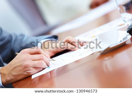 Image of businessman's hands signing documents at meeting - stock photo