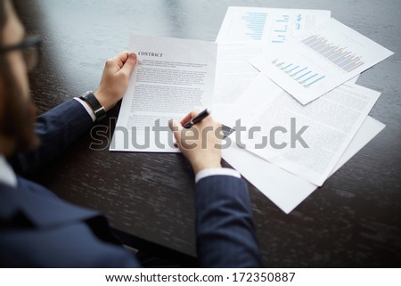 Image of businessman signing contract at workplace - stock photo