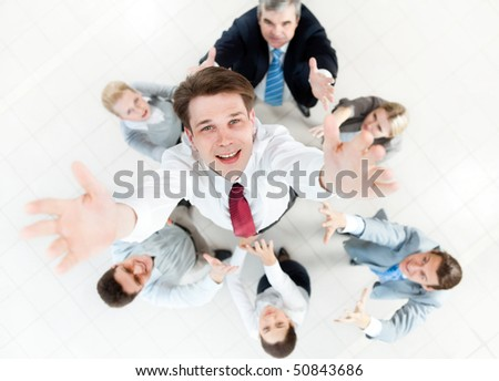Image of businessman stretching his hands to the camera surrounding by his colleagues - stock photo