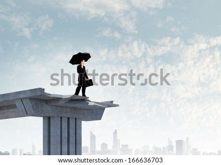 Image of businessman with umbrella standing at the edge of bridge - stock photo