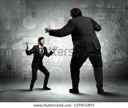 Image of businesspeople arguing and acting as sumo fighters against city background - stock photo