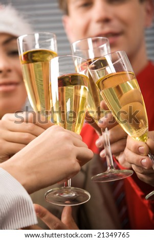 Image of businesspeople hands holding crystal glasses full of champagne - stock photo