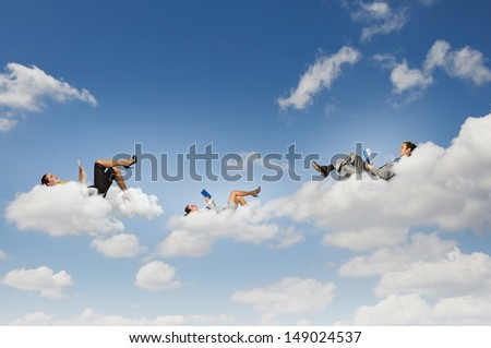 Image of businesspeople lying on clouds with tablet pc - stock photo