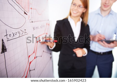 Image of businesswoman analyzing graph on whiteboard with her colleague near by - stock photo