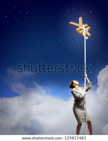 Image of businesswoman climbing the rope attached to yen sign - stock photo
