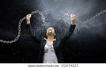 Image of businesswoman in anger breaking metal chain - stock photo