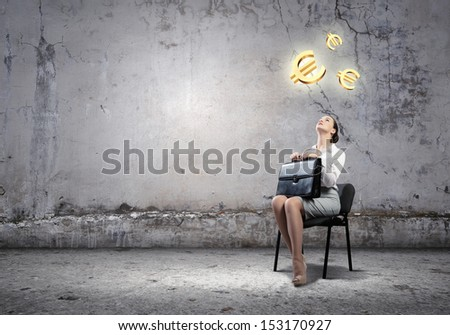 Image of businesswoman sitting on chair with suitcase in hands looking at euro symbols above - stock photo