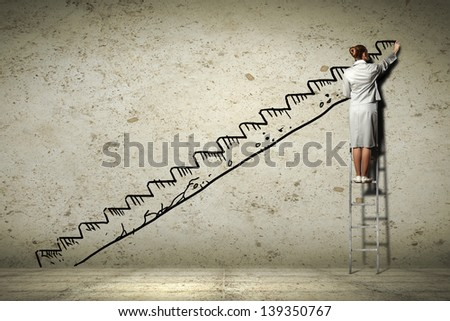 Image of businesswoman standing on ladder and drawing on wall - stock photo