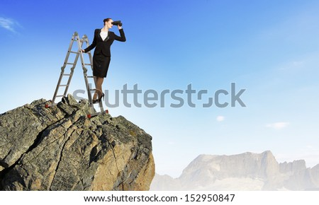 Image of businesswoman standing on ladder and looking in binoculars - stock photo