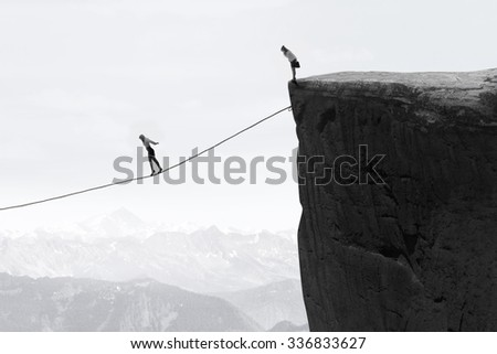 Image of businesswoman taking risk and walking on the rope over the gap - stock photo