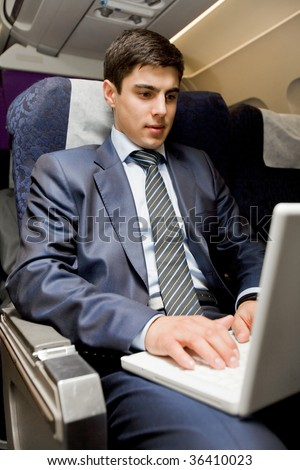 Image of busy male typing on laptop during flight - stock photo