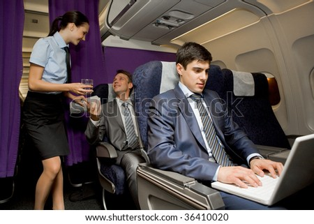 Image of busy male typing on laptop with pretty stewardess giving glass of water to successful businessman on background - stock photo