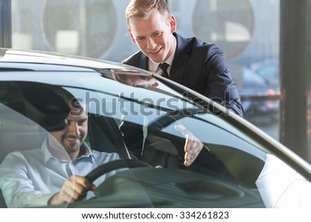 Image of car dealer with client preparing to test drive - stock photo