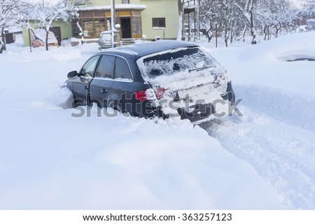 Image of Car stuck in snow near privat home - stock photo