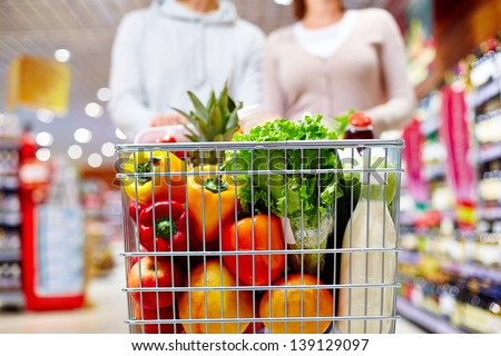 Image of cart full of products in supermarket being pushed by couple - stock photo
