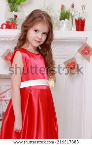 Image of caucasian smiling little girl in beautiful red dress on a Valentine's Day - stock photo