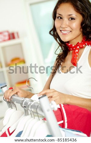 Image of charming girl choosing new clothes in clothing department - stock photo